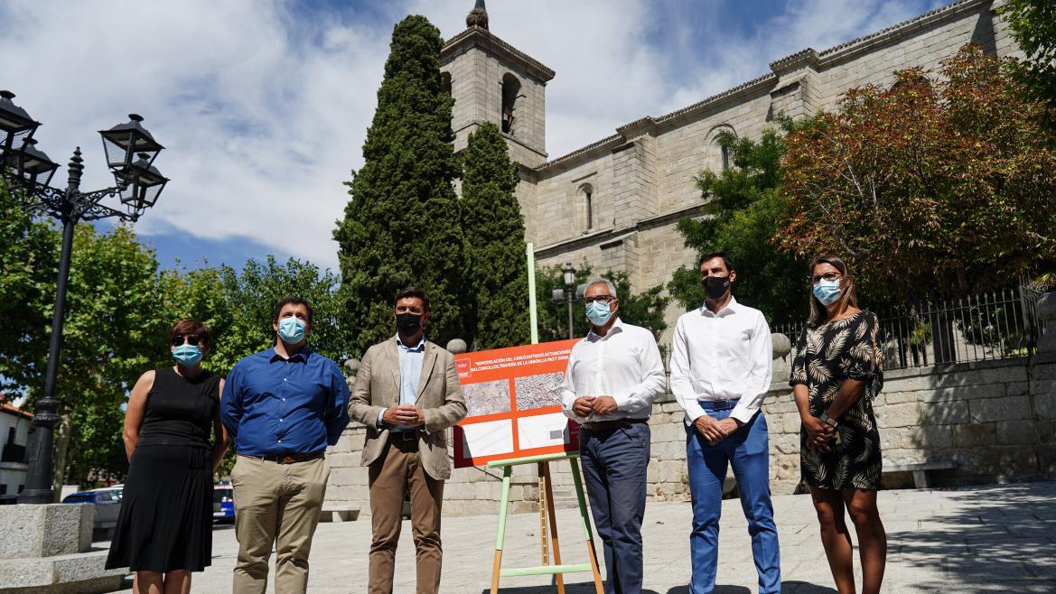 El consejero junto el alcalde de la localidad y otros asistentes posando delante de la iglesia con el cartel de las obras