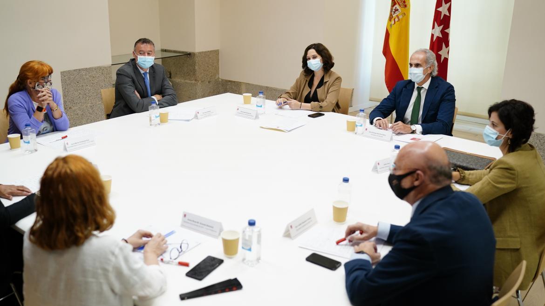 Mesa reunión consejero presidenta banderas españa sindicatos