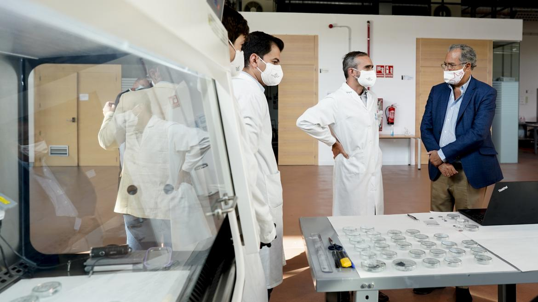 El consejero hablando con unos técnicos del IMDEA mientras miran unas muestras en unas placas
