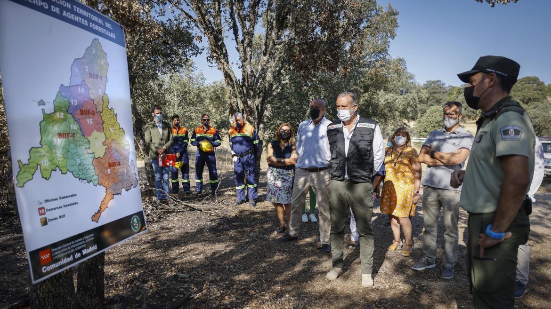 El consejero junto a más personas en el bosque observando un mapa de la Comunidad de Madrid y atendiendo a la explicación de un agente forestar