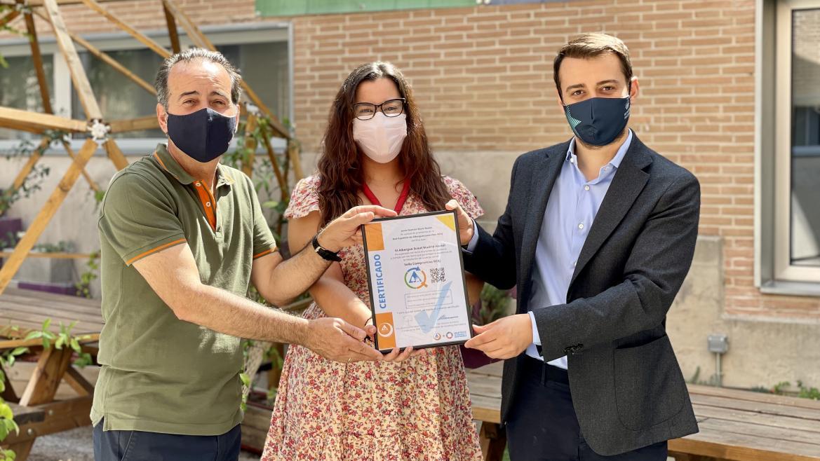 El Director General de Juventud sostiene junto con otro hombre y una mujer un marco con un certificado medioambiental