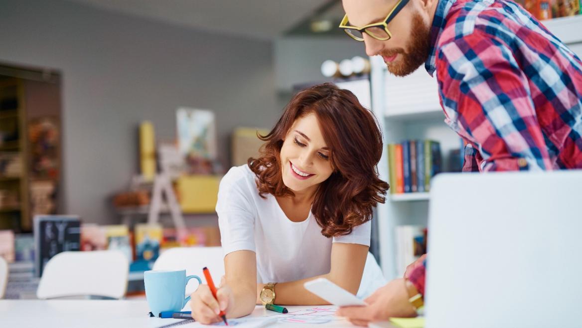Dos jóvenes trabajando en una oficina frente a un ordenador
