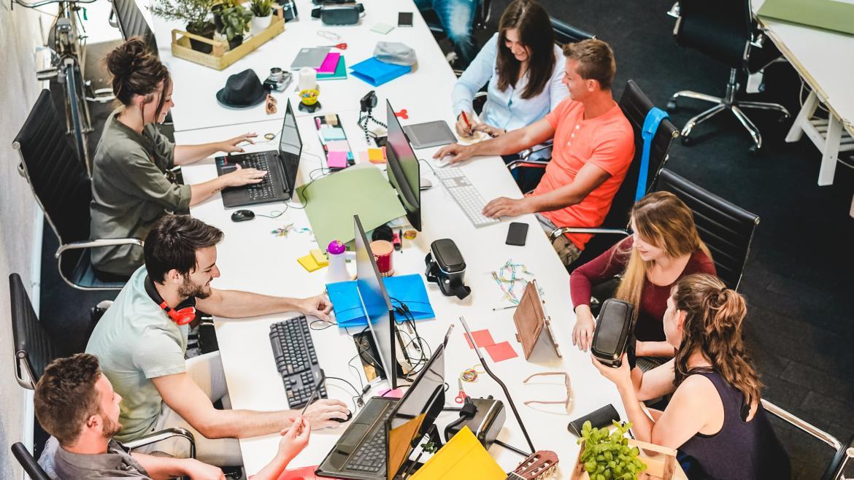 Grupo de personas jóvenes trabajando alrededor de una mesa