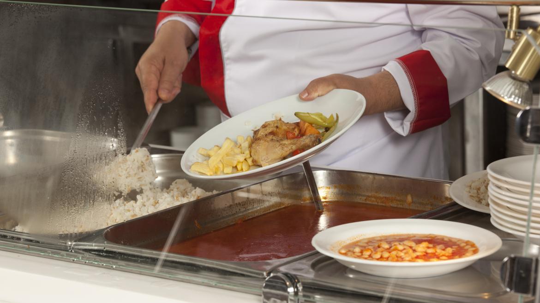 Una mujer sirve un plato de comida en un comedor