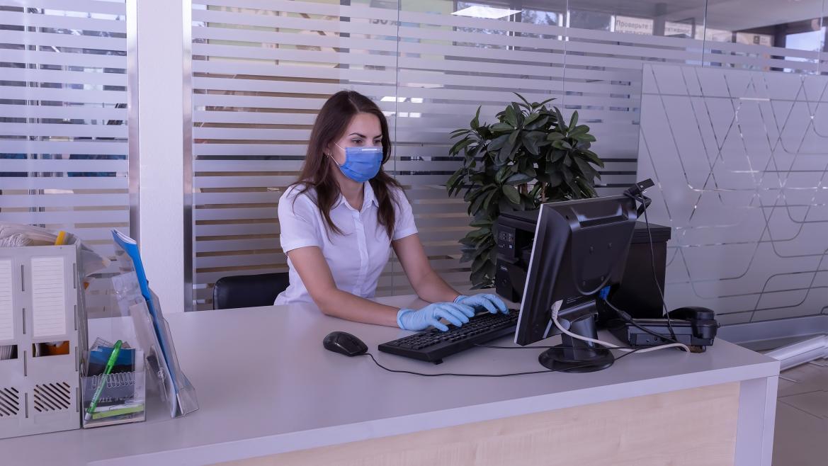 Una mujer trabaja frente al ordenador con mascarilla