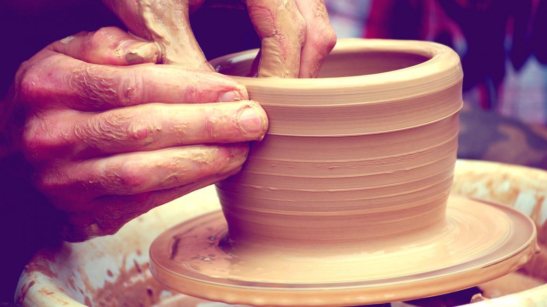 La mano de un artesano moldeando un jarro de cerámica
