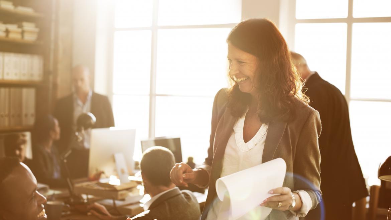 Una trabajadora en una oficina de pie sostiene un papel mientras sonrie