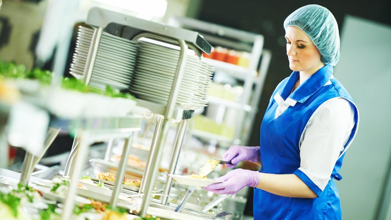 Una mujer sirviendo comida en un comedor