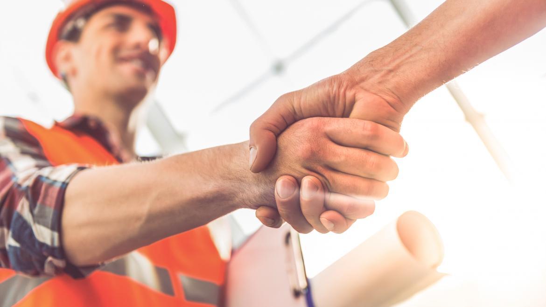 Un hombre con un casco de obra da la mano a otro hombre