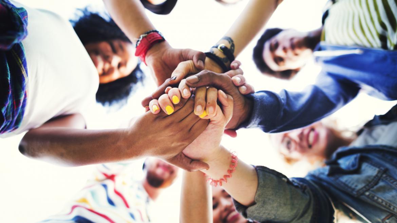 Jóvenes juntando las manos en el centro