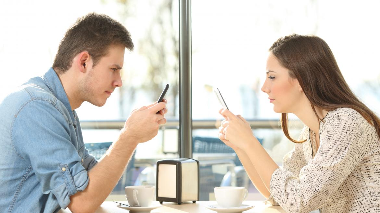 Un hombre y una mujer sentados frente a frente en una cafetería, cada uno está mirando la pantalla de su móvil