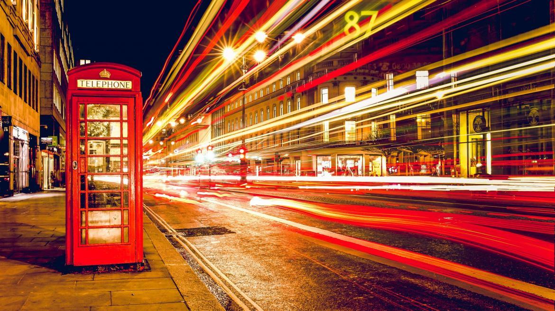 Cabina de teléfonos típicamente inglesa con luces de tráfico de la calle en la noche