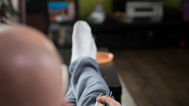 señor sentado en el sofá con el mando a distancia en la mano viendo la tv