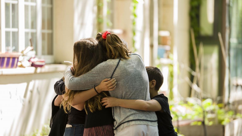 Niños abrazándose en el jardín del Hospital