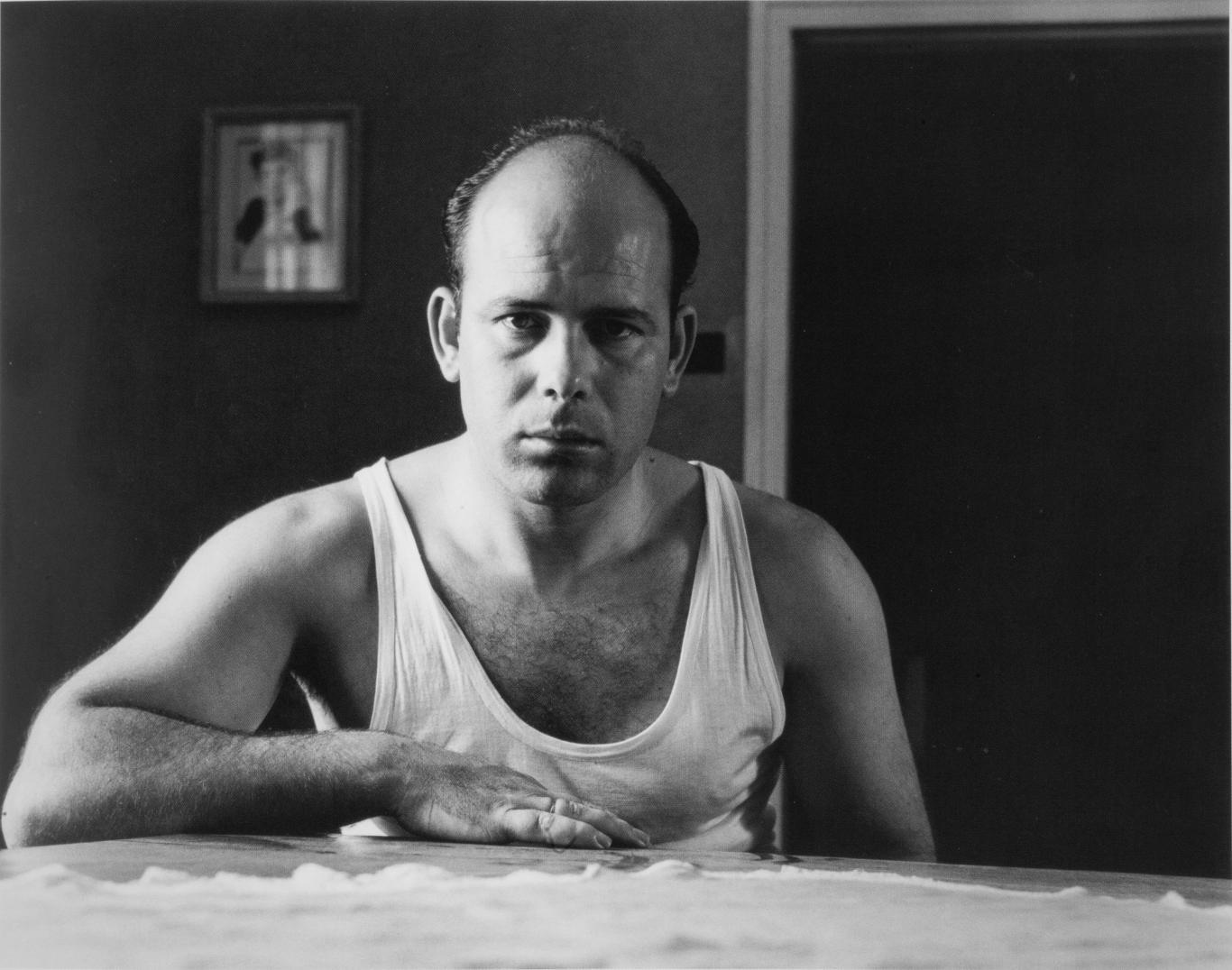 Autorretrato del fotógrafo Cualladó, sentado y con camiseta de tirantes blanca mira al espectador