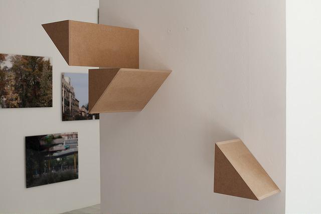 Instalación artística con fotografías  entremezcladas con figuras geométricas hechas en madera con formas piramidales, todo ello colgado en la pared