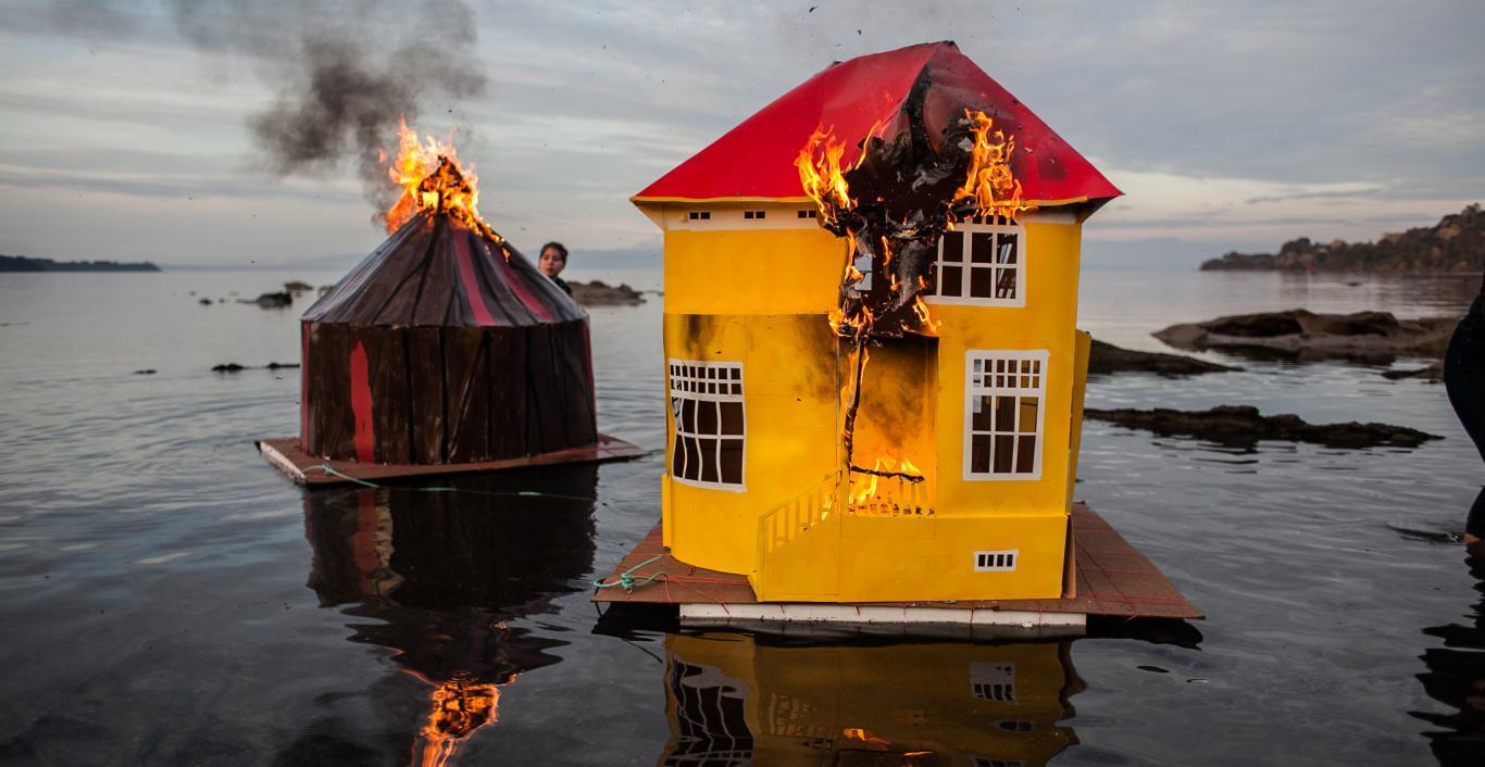 Maqueta de casa y carpa de circo ardiendo y flotando sobre agua