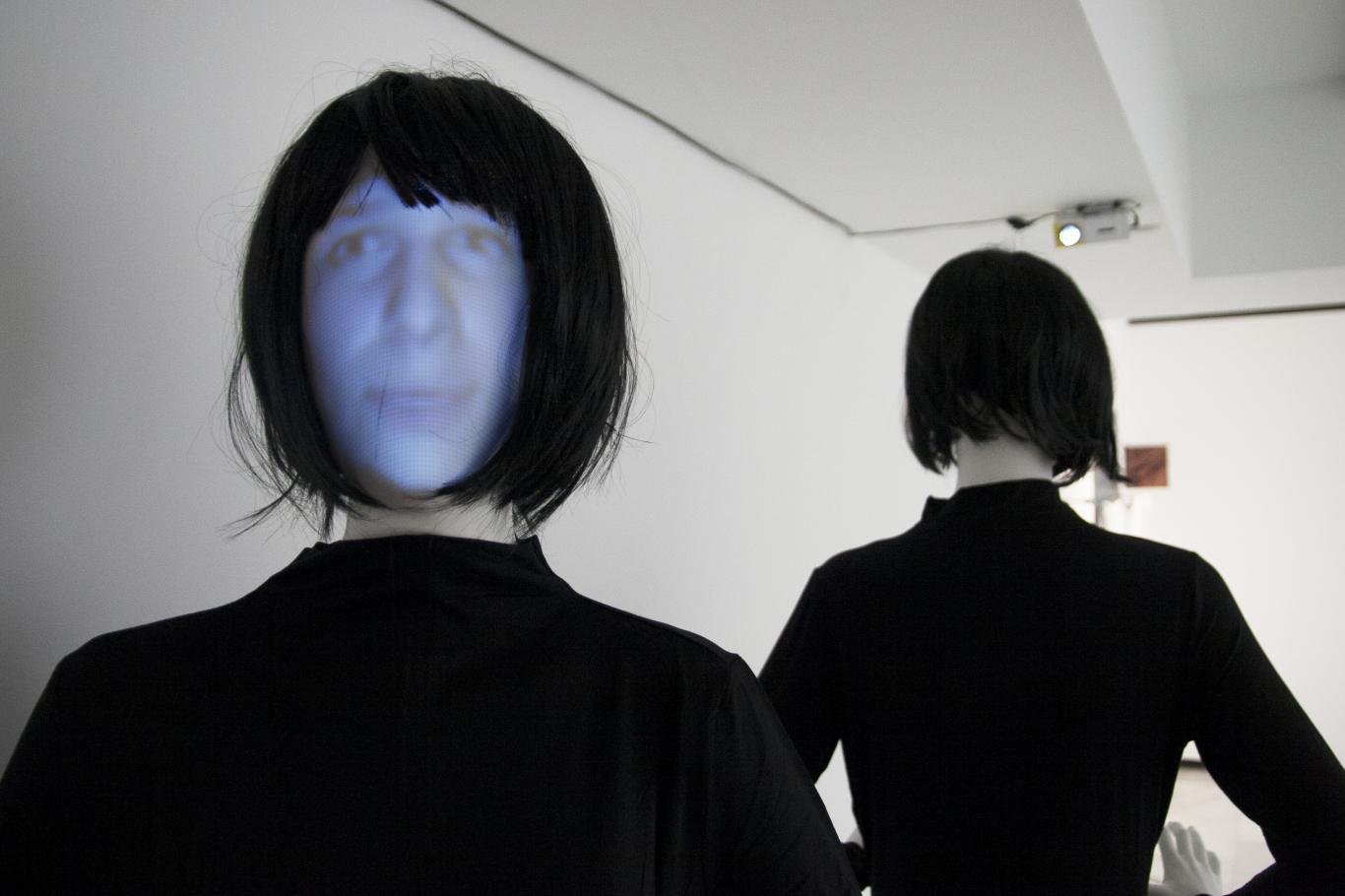Dos maniquís con pelucas negras y proyecciones de rostros en sus caras