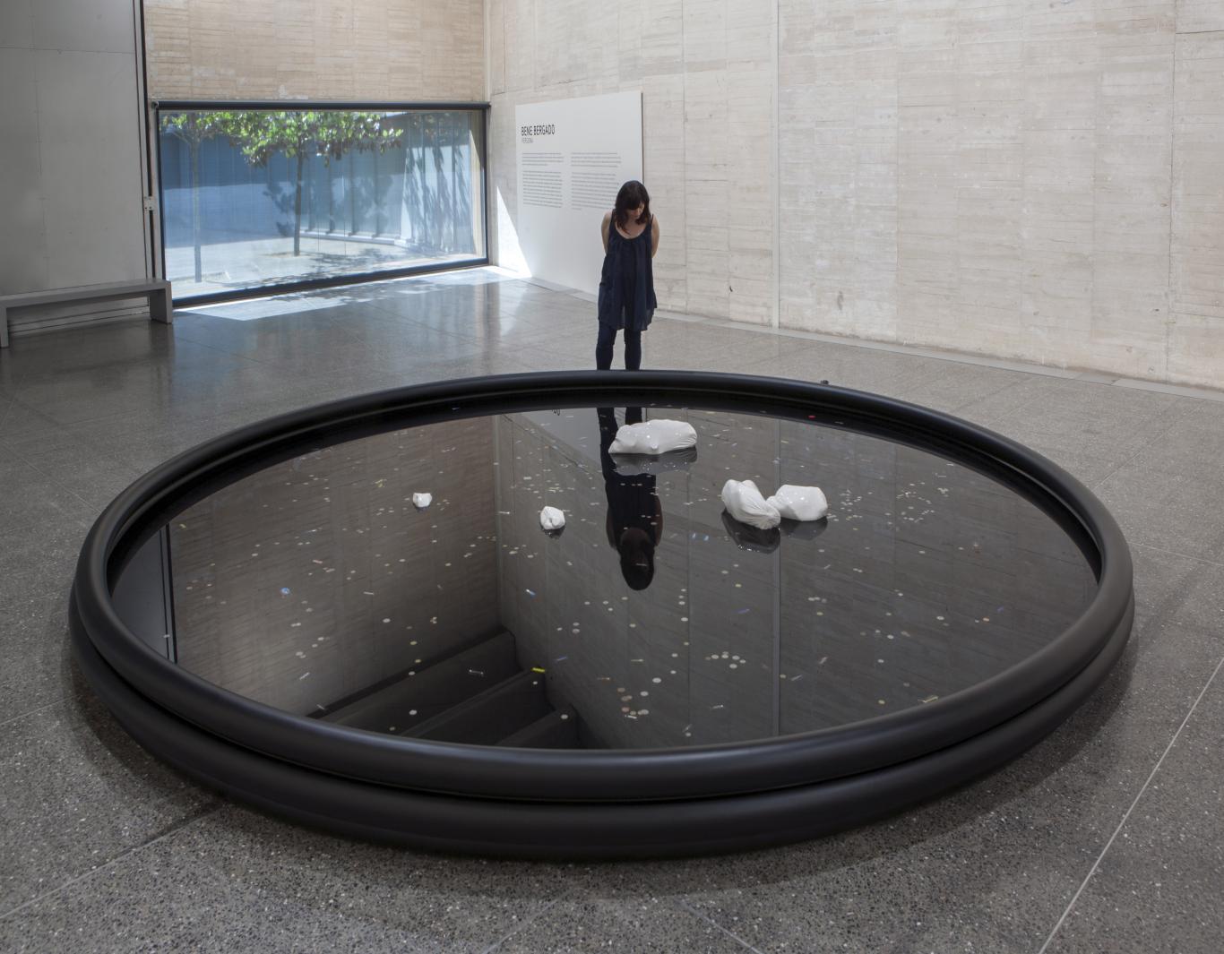 Mujer mirando una instalación de una piscina hinchable negra en el suelo, con agua y unos patos de cerámica