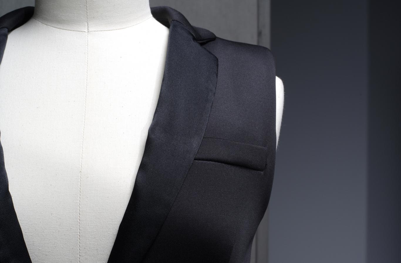 Detalle de un maniquí blanco vestido con un chaleco con solapa negra