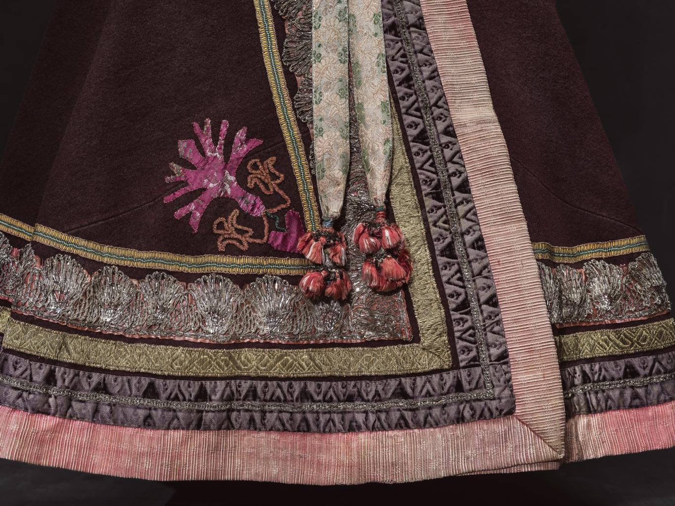 Detalle de un vestido regional de mujer en el que se ve parte de la falda y mandiles bordados y con aplicaciones vegetales y florales