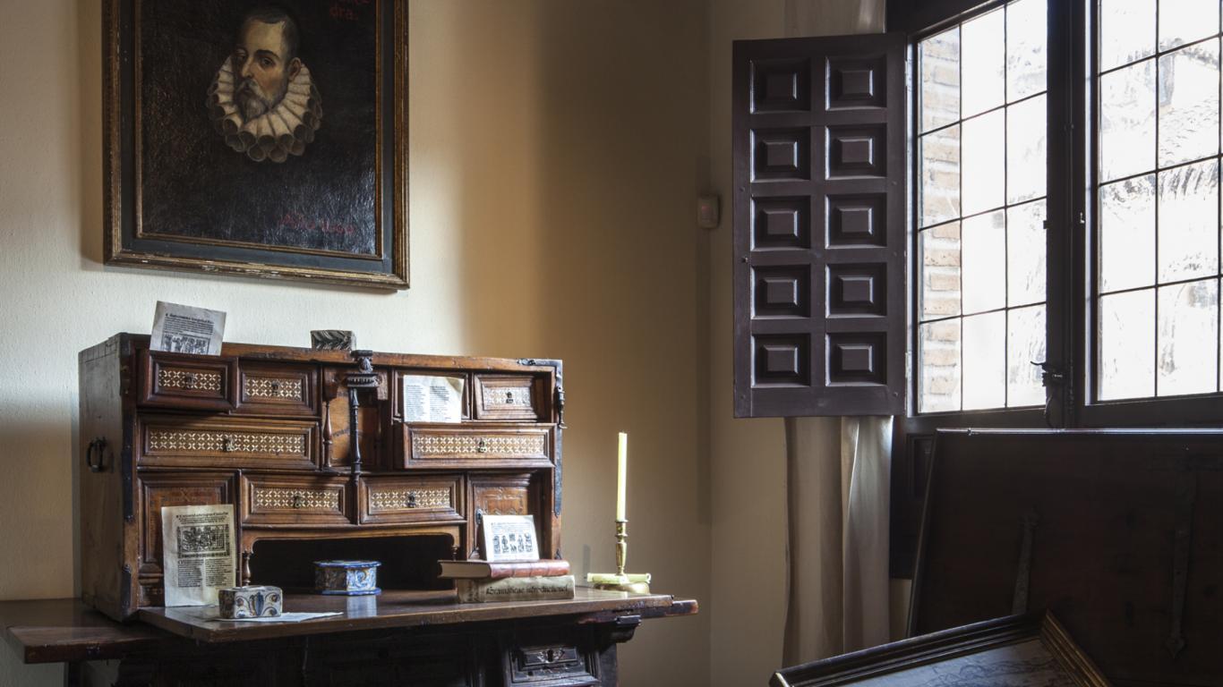 Habitación con un escritorio antiguo y un cuadro de Cervantes en la pared