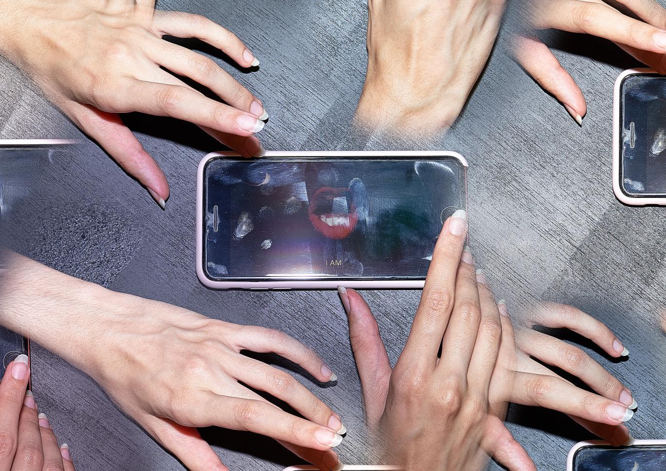 Varias manos en círculo cogiendo móviles