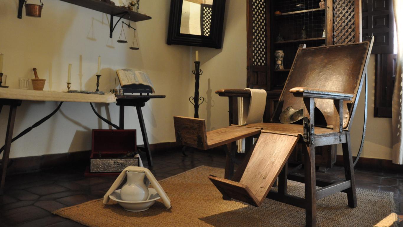 Habitación con una silla de madera y botes de farmacia antigua