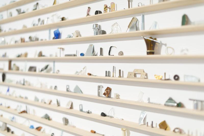 Instalación artística hecha con pequeñas estanterías de madera dispuestas en horizontal con pequeños objetos sobre ellas