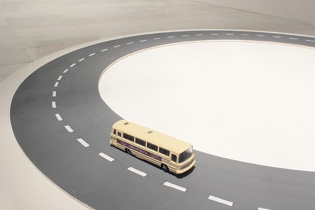 Instalación artística que simula una carretera y un autobús amarillo de juguete sobre ella
