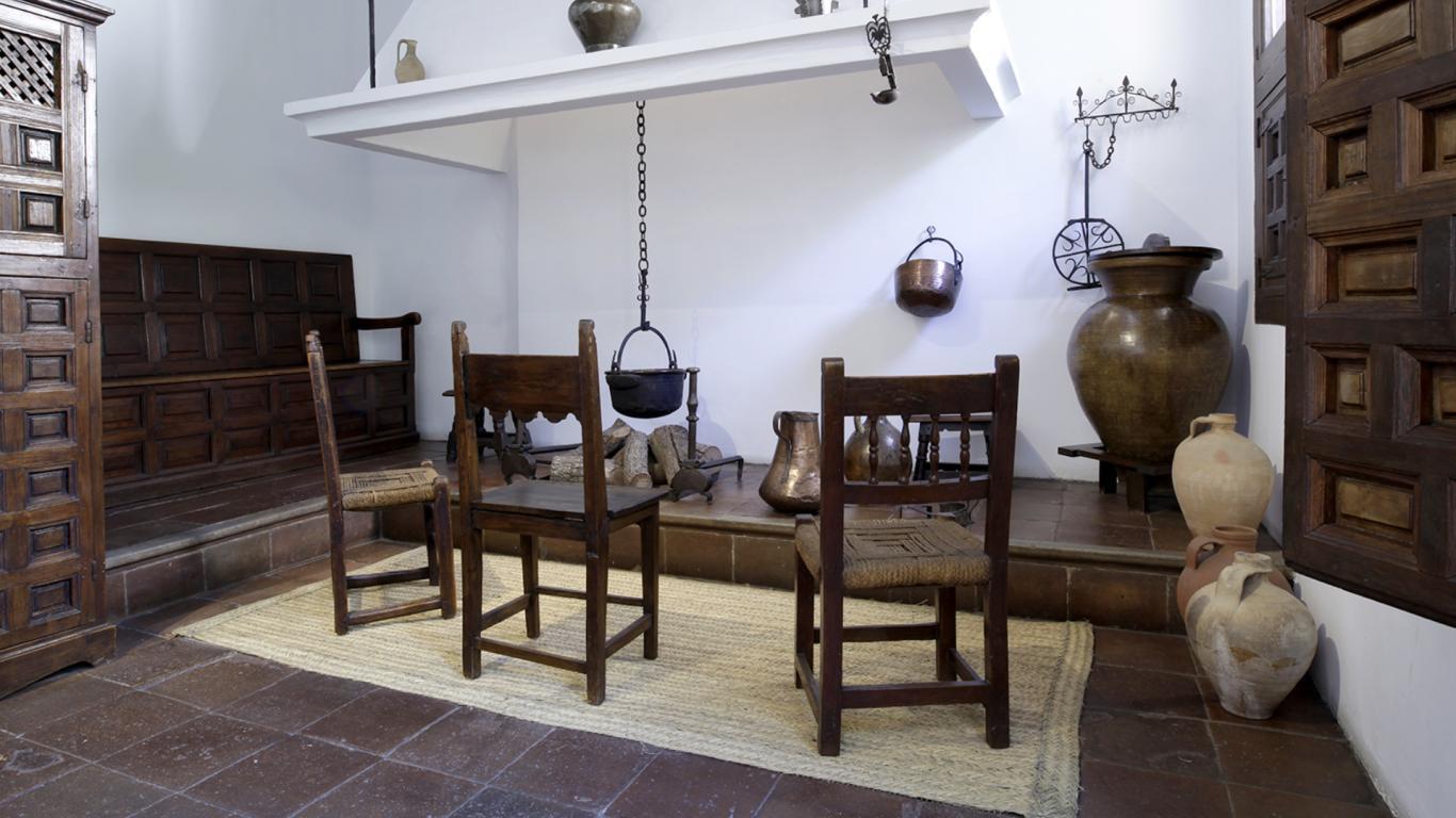 Cocina antigua con chimenea, dos sillas de madera y objetos de hierro y latón