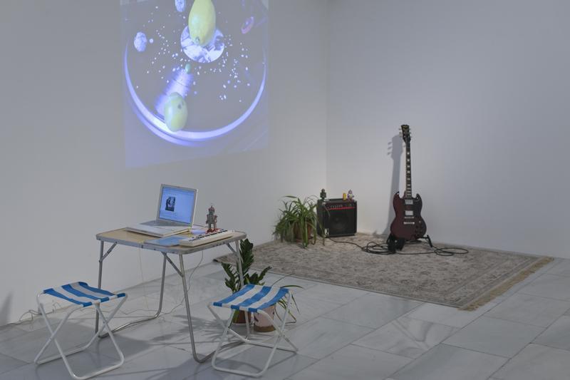 Instalación artística con piezas diversas como una mesa, un ordenador, una alfombra, una guitarra eléctrica