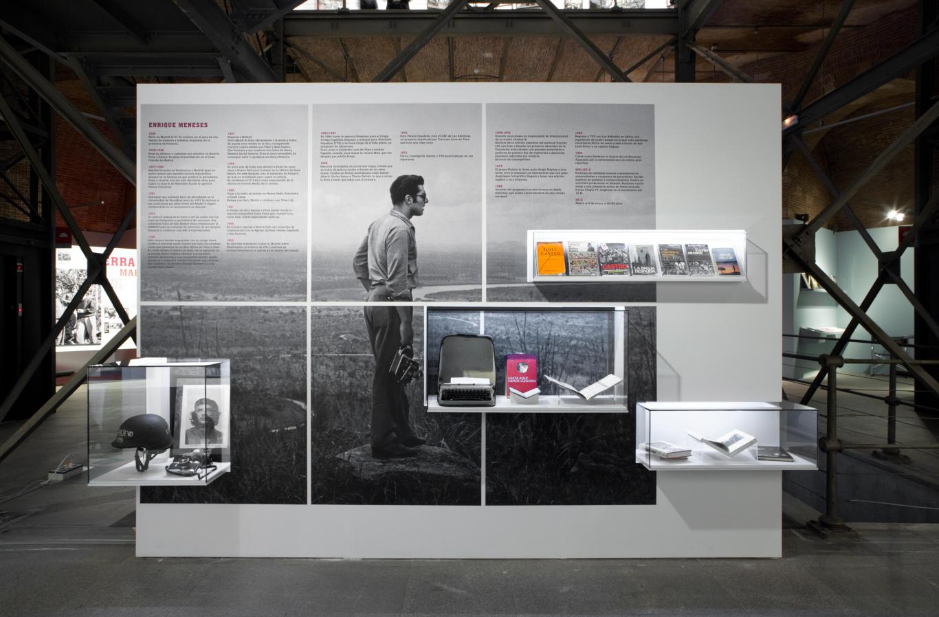 Panel con texto, libros e imagen del fotógrafo Enrique Meneses con su cámara en un paisaje exterior