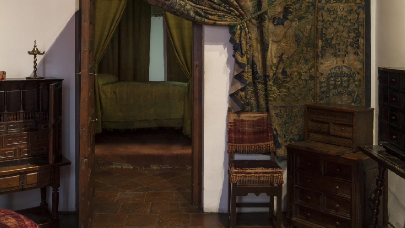 Entrada a un dormitorio antiguo con dosel y colcha en verde