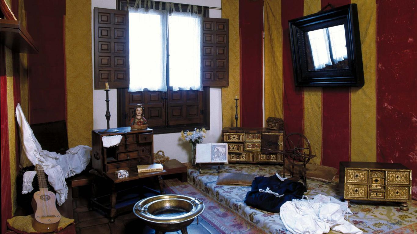 Habitación con tarima en el suelo, tapices, alfombras, brasero antiguo y piezas de hogar