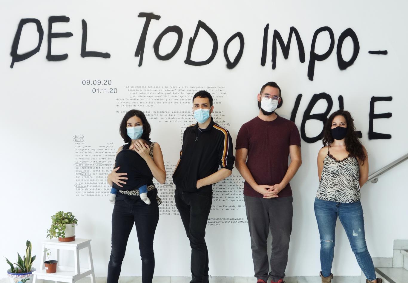Cuatro jovenes posan frente a un muro con un grafiti donde se lee Del todo imposible