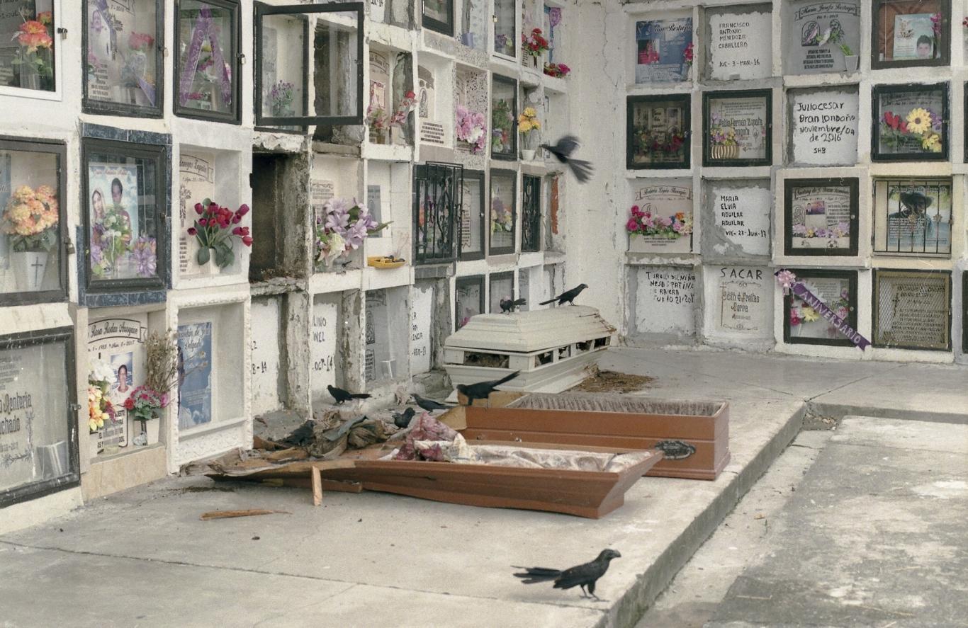 Foto de un cementerio con niños y dos ataúde en el suelo