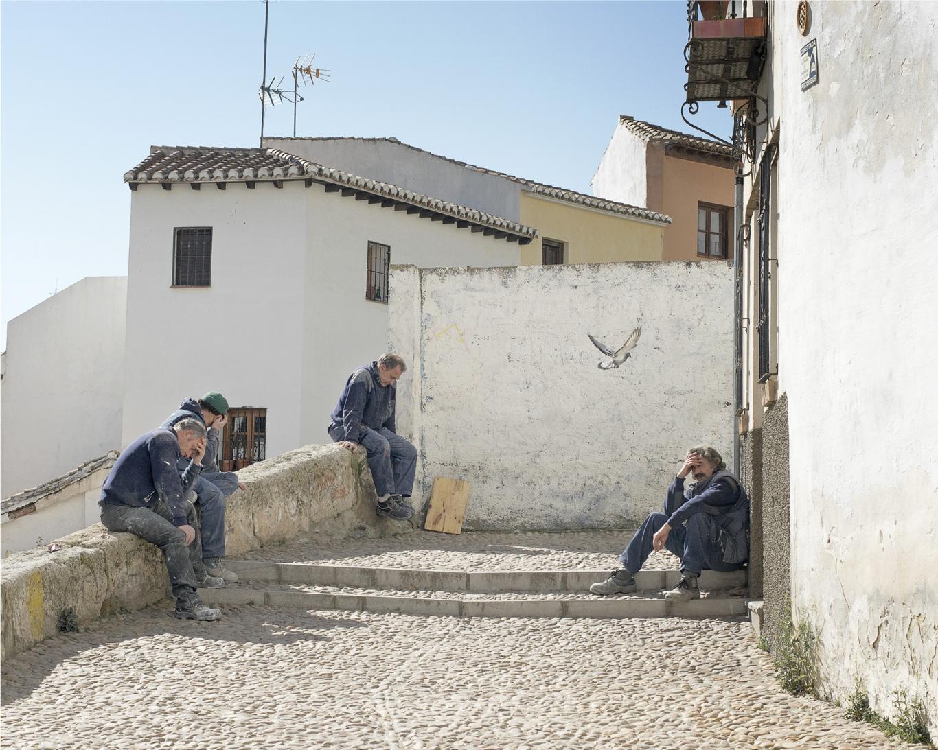 Hombres mayeres sentados en unas escaleras de un pueblo