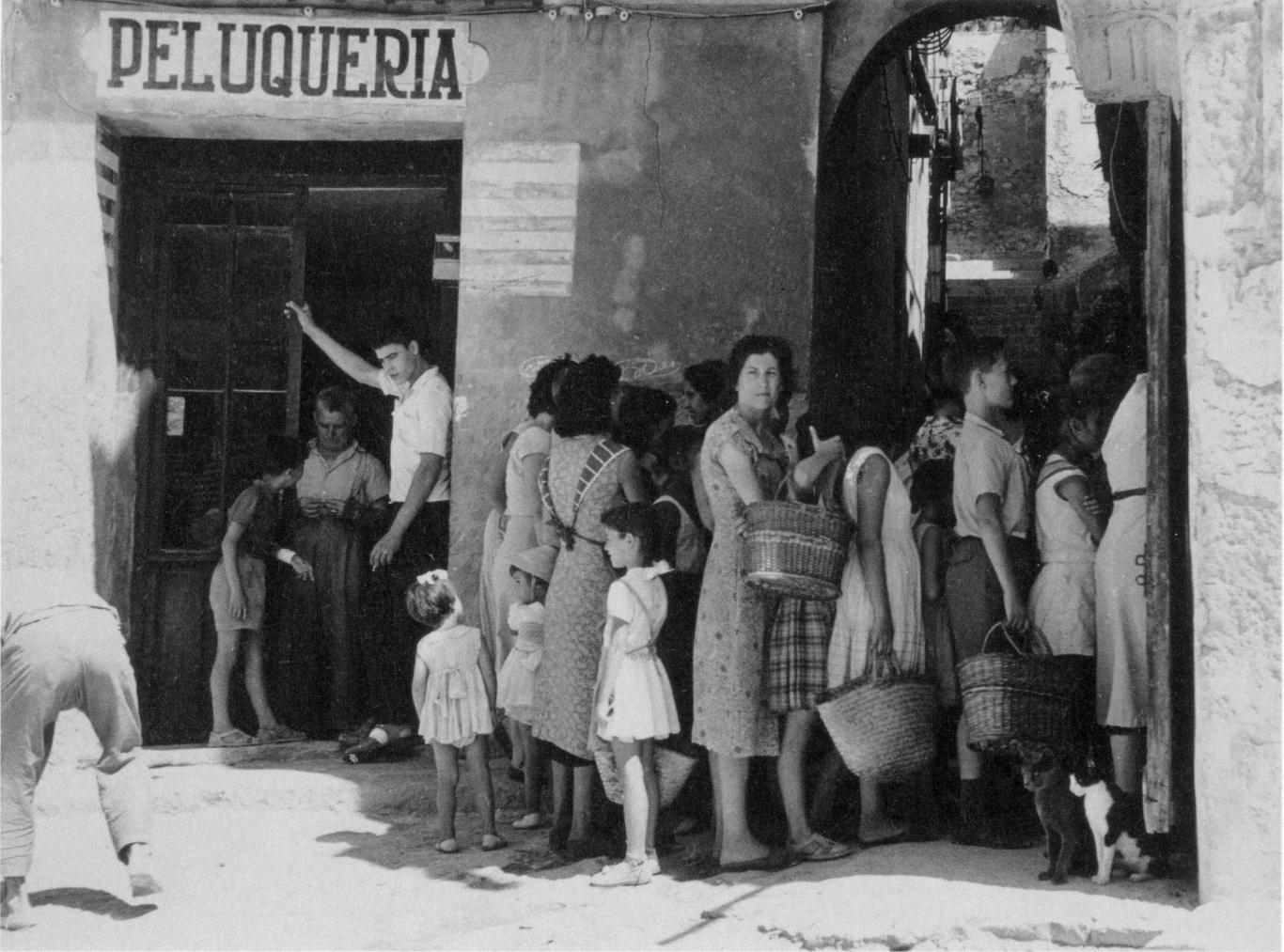 Foto en blanco y negro con gente haciendo cola en la puerta de una peluquería antigua