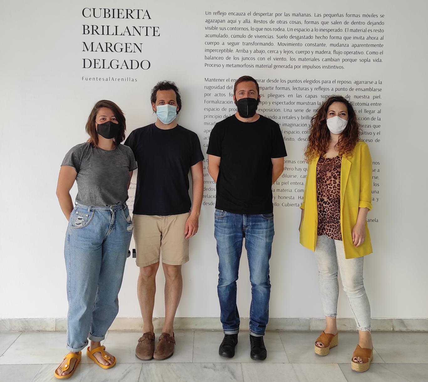 Retrato de cuatro personas frente al cartel de la exposición