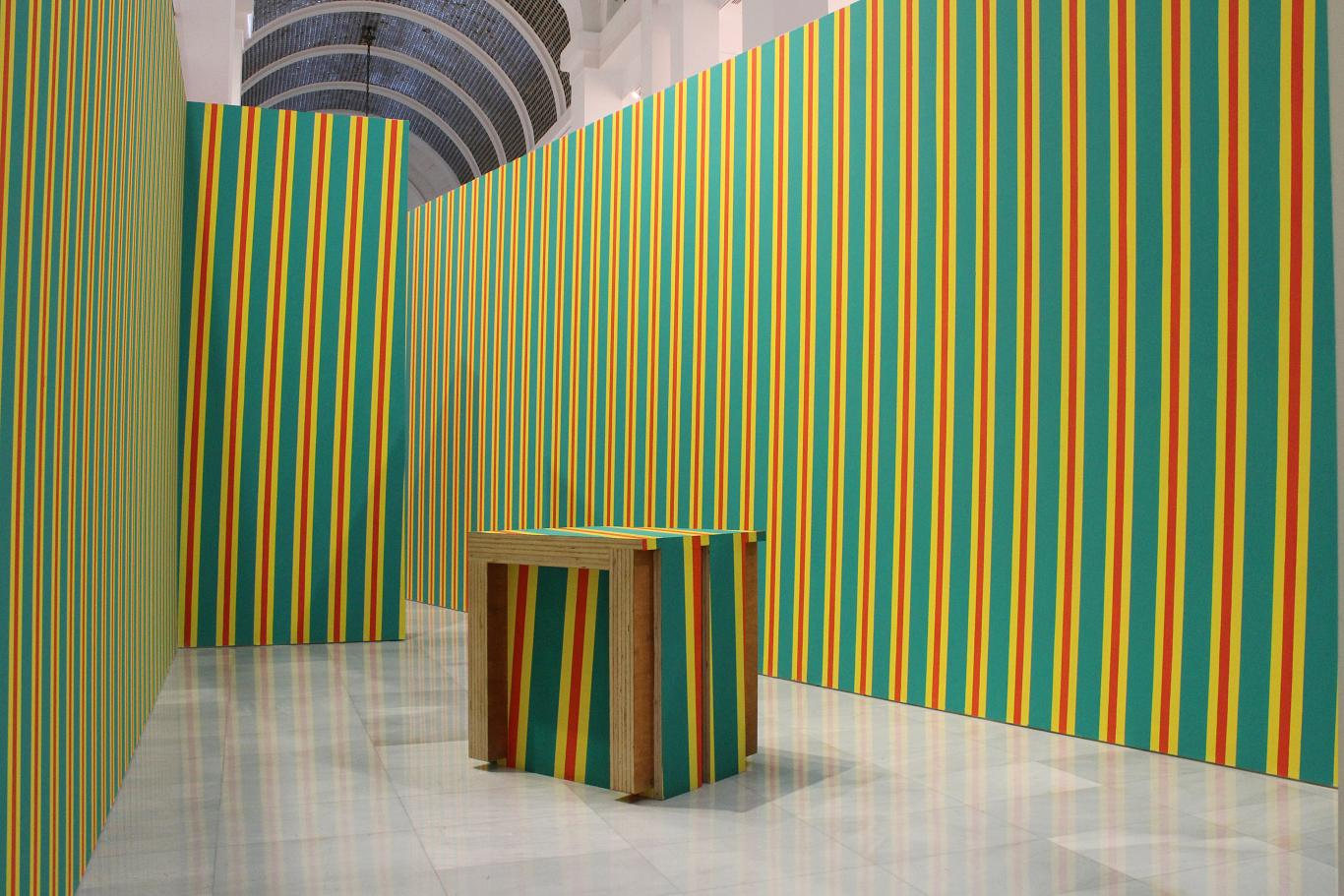 Muro pintado con rayas de colores en vertical en tonos verdes, amarillos y naranjas realizado por Pello Irazu. Un cubo en el centro repite el mismo patrón de dibujo