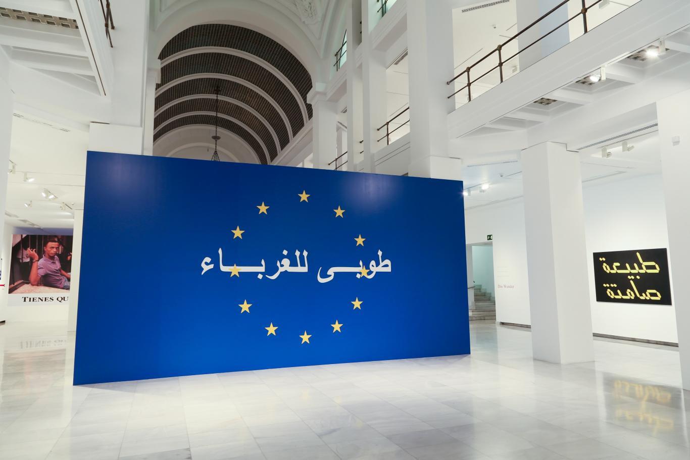 Muro pintado de azul en la entrada a la Sala Alcalá 31. Se distinguen 12 estrellas en dicho panel a modo de bandera de Europa y unas letras en árabe sobre ella