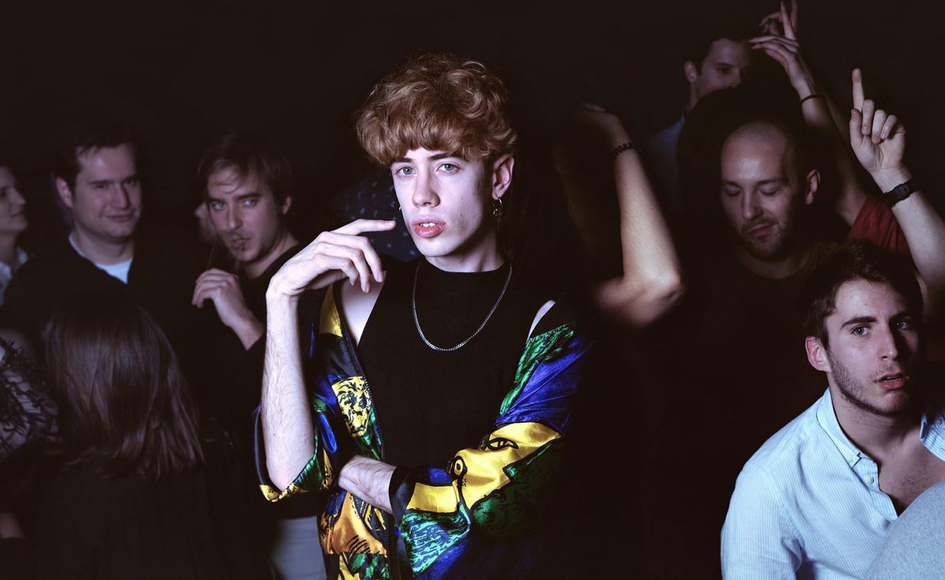 Joven pelirrojo rodeado de otros jóvenes bailando