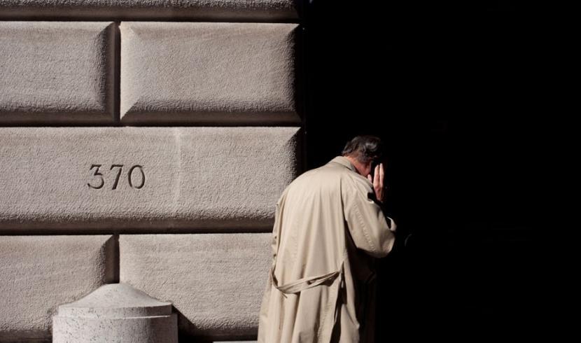 Hombre con gabardina y de espaldas hablando por un móvil