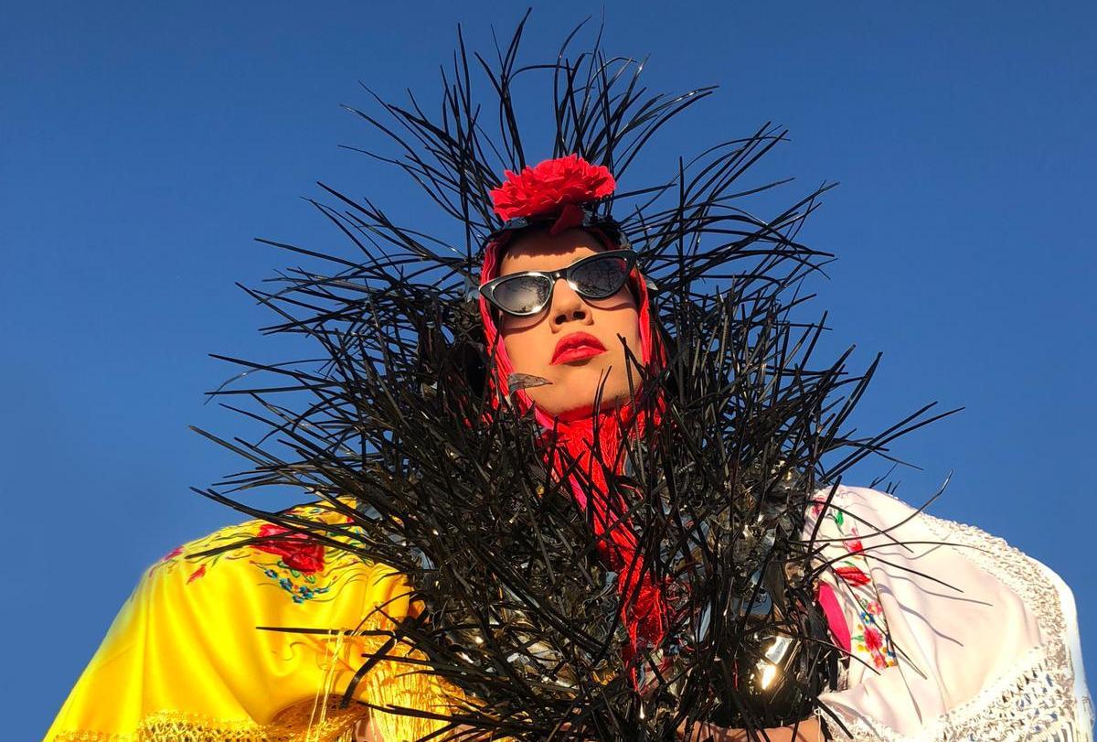 Retrato de una mujer con turbante, gafas de sol y plumas
