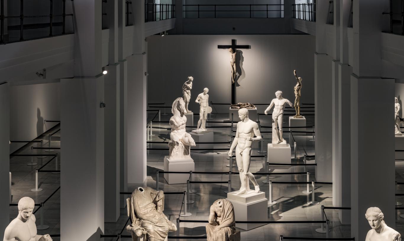 Vista de la Sala Alcalá 31 con la instalación de Mateo Maté en la que hay una suerte de laberinto hecho con catenarias negras y, en los espacios,, se ubican esculturas clásicas y religiosas