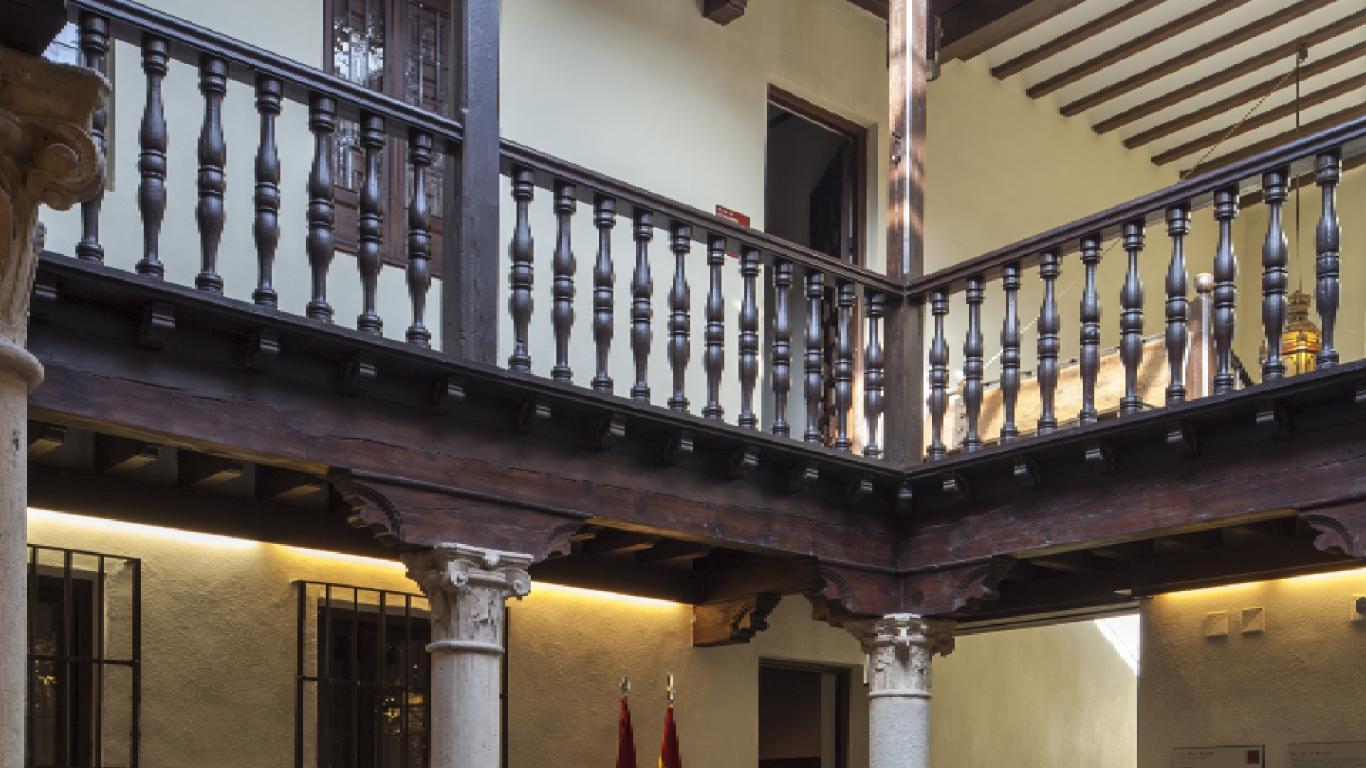 Vista de un patio interior con dos alturas y una barandilla de maderar en la planta superior