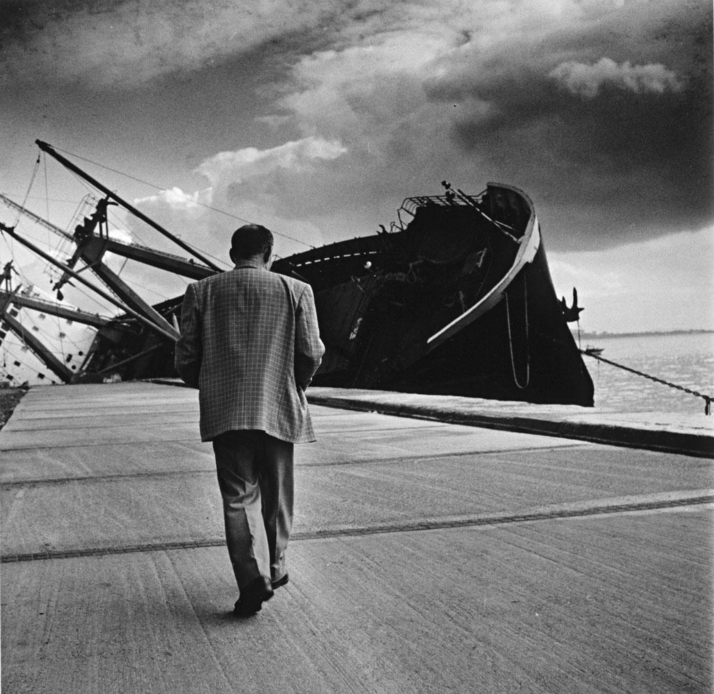 Imagen en blanco y negro con un hombre de espadas andando hacia un barco hundido