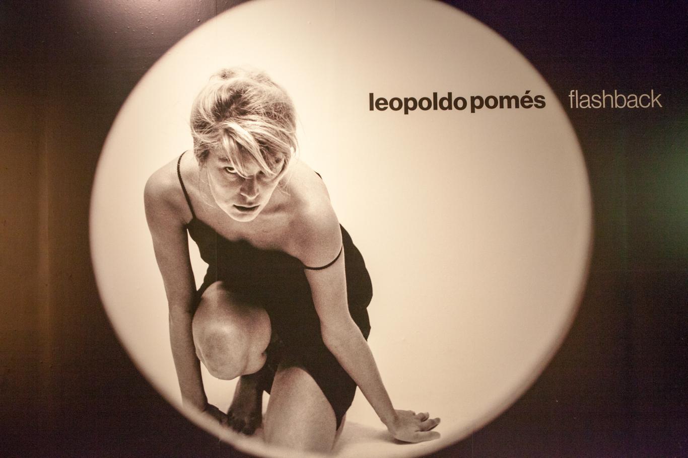 Foto de Leopoldo Pomés que es un recorte circular que enfoca a una modelo rubia arrodillada y con vestido negro que mira a la cámara