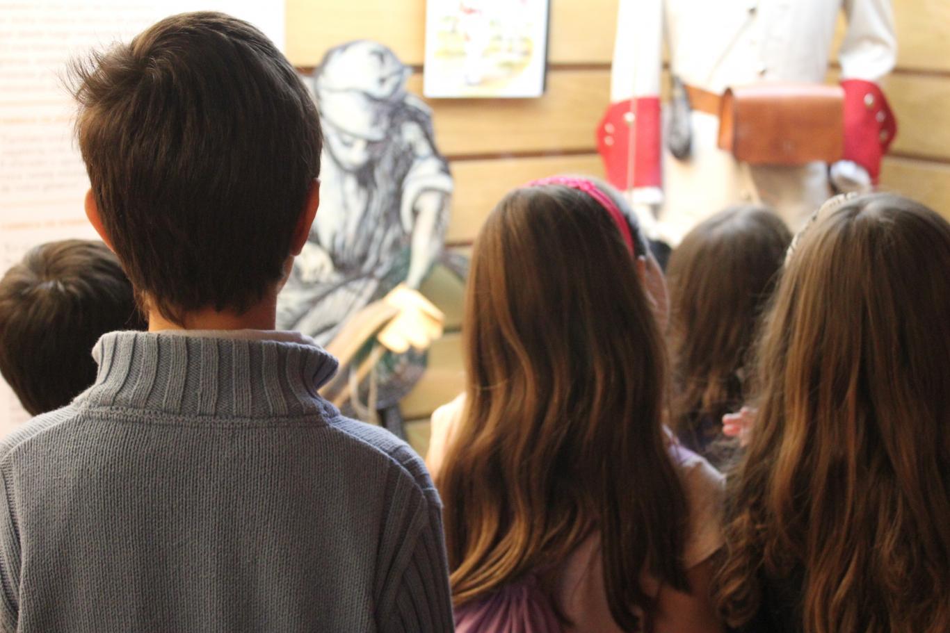 Grupo de niños y niñas observando una vitrina sobre textiles y uniformes en el Centro de Interpretación de Nuevo Baztán